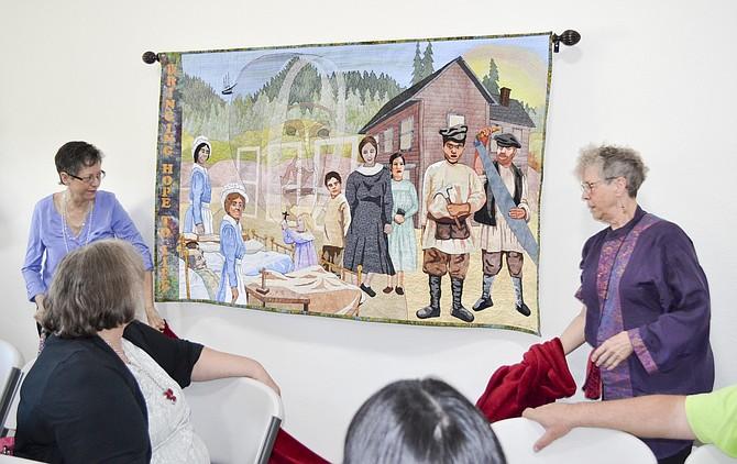 Mimi Hubert  of St. Louis, MO., sister of  Valley artist Deborah Ann unveiling a piece of hanging artwork  during last Friday's  dedication ceremony at Mother Joseph Villa housing development in Granger .