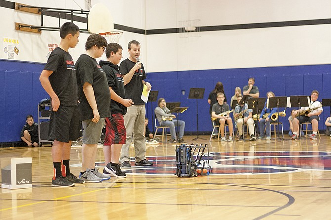 Ryan Nguyen, left, Gavin Boyson and Kahl Murdock, demonstrate how their robot works during an assembly at LaCreole Middle School on April 13. Coach Jacob Gradek, right, will accompany the team to the robotics world championships in Louisville, Ky. this week.