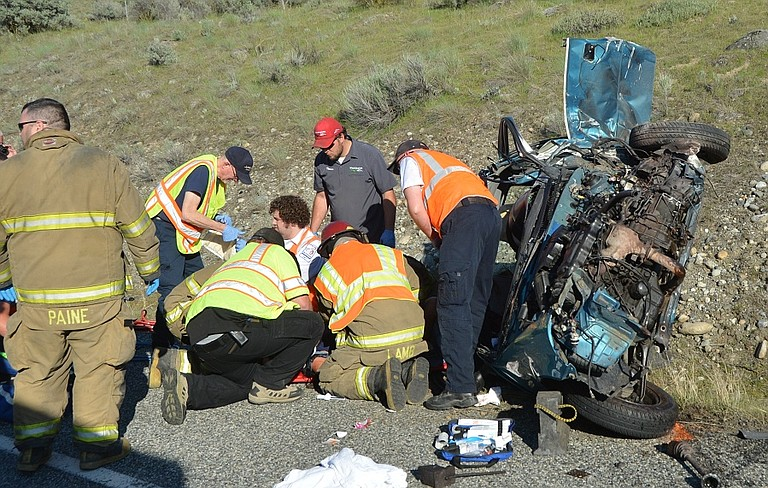 Workers rescue a woman from her vehicle involved in a crash on Highway 97 adjacent to Okanogan.