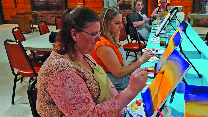 Ginny Heard and Sarah Jobe focus on brush strokes at the Party While U Paint event at the Independence Elks Lodge on Saturday. The class, taught by Tamara Kime, helped participants create a forest scene. For more, see Explore Polk County on May 25.