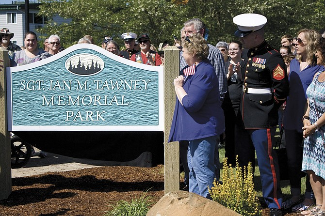 U.S. Marine Sgt. Ian Tawney's mother, Theda Tawney, center holding flag, looks over the unveiled sign at the newly dedicated park named after her son on Saturday. A large crowd gathered at the park near Main Street and Walnut Avenue in Dallas for the ceremony, which included the Marines, the Patriot Riders and Dallas Fire & EMS. The park was named after the city of Dallas held a poll for citizens to vote on suggested names.