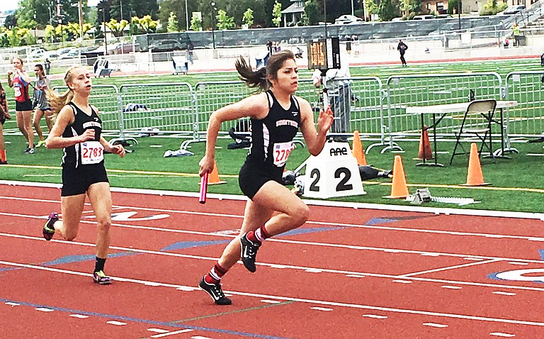 Janessa Frank  left, slows after a successful exchange to Jeniya Guillen during the 1,600 meter relay.
