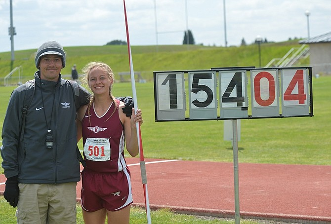 Okanogan coach Zach Spate and Emmy Engle pose next to 154 foot, 4 inch mark Engle posted on her final javelin throw at state Friday afternoon.