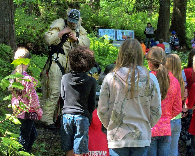 """Students from Clearwater Valley Elementary School learn smoke jumping """"suiting up""""  techniques from Rye Phipps, Grangeville smokejumper, at O'Hara Campground, Moose Creek Ranger District."""