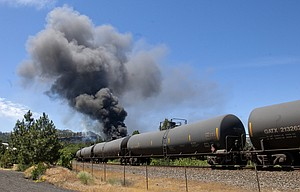 A train carrying Bakken crude oil, a type of oil known to be highly volatile, sits alongside a public parking area in downtown Mosier after derailing and catching fire around noon on Friday.