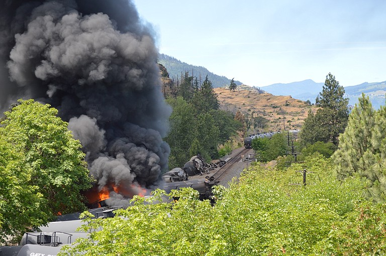 Fire rises from an oil train car derailment on the Union Pacific tracks in Mosier.