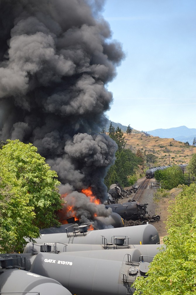 FLAMES ROAR from derailed oil tankers in Mosier Friday afternoon, seen facing west from the Rock Creek overpass. The 96-unit Union Pacific train likely left the tracks due to a faulty bolt that fastens the rail to the railroad ties, company representatives said. The community of about 400 is still recovering as multi-agency crews work to clean up the scene.