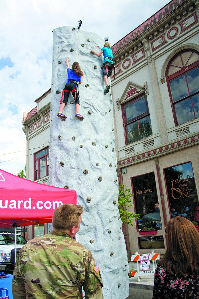 Katie Dufner and Presliegh Dodds climb the National Guard's rock wall on June 7 at the city of Dallas' Tuesday on the Square event downtown, the first of four the city will host.