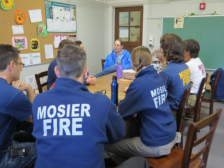SEN. RON WYDEN, back, meets privately with Mosier firefighters Sunday to learn how their experiences affected the small community, as well as themselves as individuals.