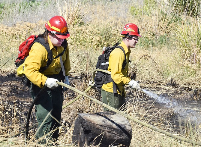 Yakama Nation and Yakima County Fire District No. 5 firefighters extinguish a grass fire on Plank Road south of Granger yesterday. Crews were called to the scene at about 4 p.m. The fire threatened a home and multiple vehicles, burning about 2.5 acres and an older model flatbed truck before it was doused. Capt. Joel Byam said the fire was the result of a burn getting out of control.