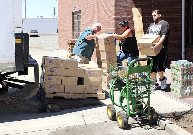 Sunrise Outreach Director of Operations Ken Trainor, left, works with food bank volunteers during the move to the new food bank location, at 529 S. Ninth St. The food bank reopens tomorrow at 9:30 a.m.