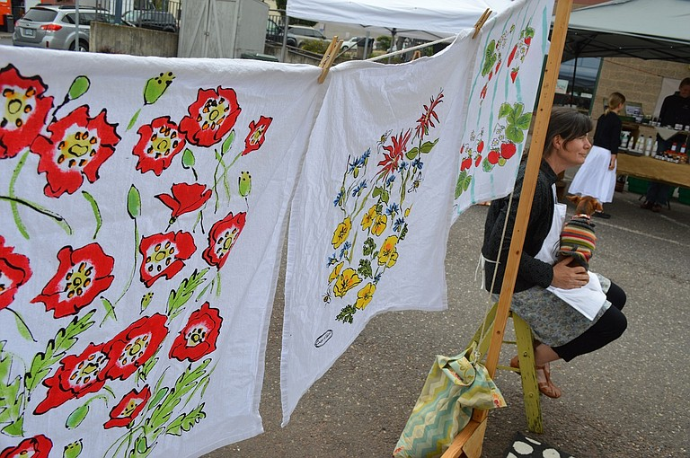 Lynn Lewis, of Crisp and Tart, displays her hand painted, 100 percent cotton kitchen towels at a recent Saturday market.