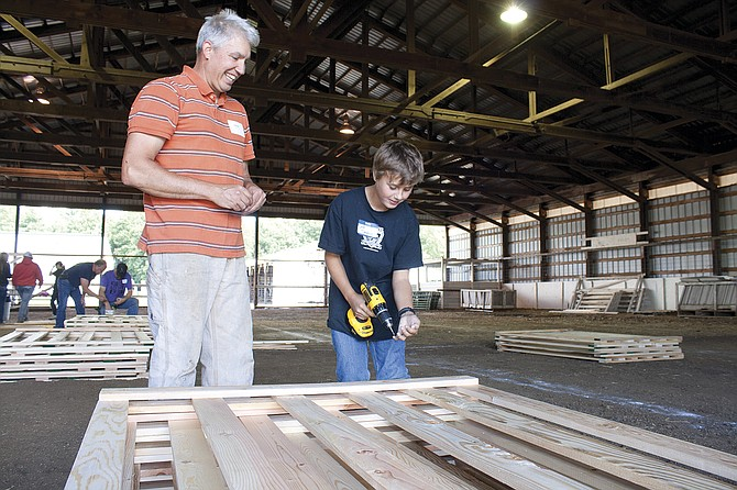 "Jeff Tompkins, 10, right, takes a lesson in building goat pens from Steve Anderson on Saturday during ""Polk County Fairground Beautification Day."" The event is part of the Polk County Ford Institute Leadership class. A number of volunteers also helped out."
