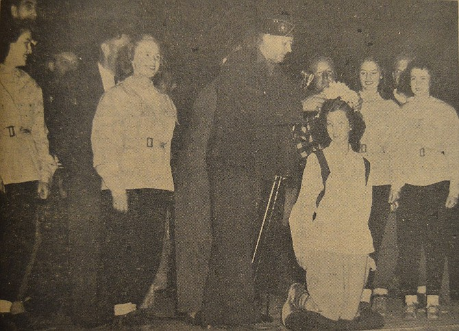 "August 2, 1946 — ""I crown thee Queen of the Legion Climb,"" says J. Dayton McLucas as he places the coronet of avalanche lilies on the head of Queen Dorothy Beachman in the Saturday evening coronation ceremony at the open-air Legion camp amphitheater. To the right of McLucas are Princesses Betty Level and Evelyn Kresse and to the left are Princesses Virginia Wilson and Betty Jean McIsaac. The ceremony took place during the Saturday presentation at the Legion climb."