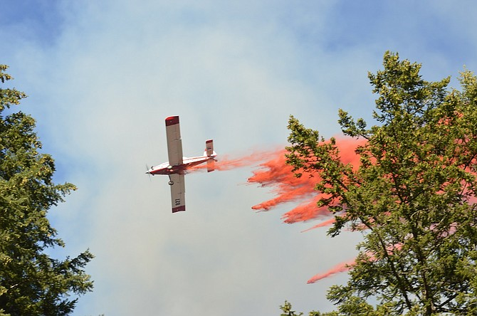 PLANE drops a jet of crimson fire retardant over a wildfire near south Neal Creek Road.