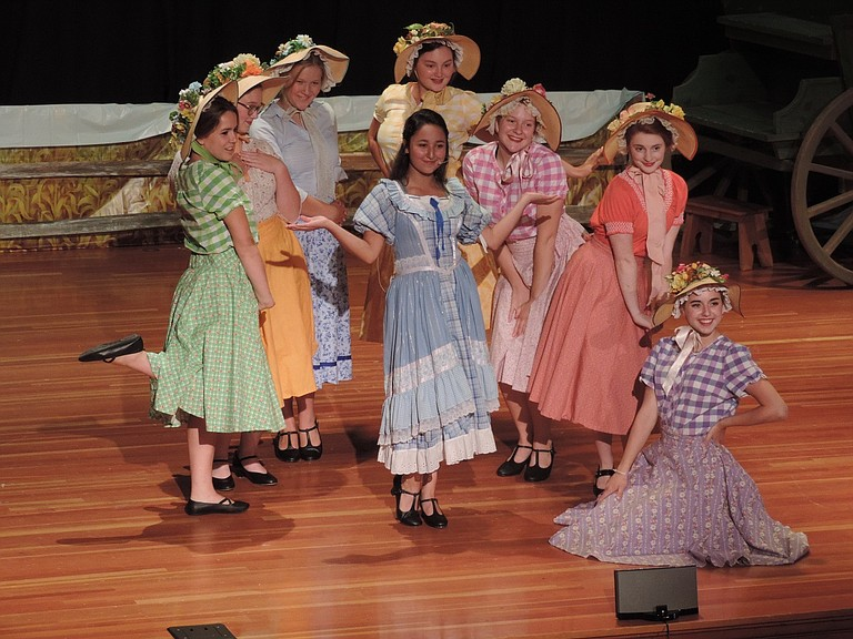 "'Oklahoma!' continues run: Catch '""Oklahoma!"" at the Hood River Middle School auditorium this weekend, Aug. 12-13, for shows beginning at 7:30 p.m. Presented by Plays for Non-Profits and directed by Lynda Dallman, the musical will benefit Next Door, Inc., and Columbia Dance Academy — the ballet sequence and several other dance numbers feature Academy dancers. Tickets are $15 for students and seniors, or groups of 10 or more, and $20 for adults; buy online at showtix4u.com, at the door, or at Waucoma Bookstore. The play runs just over two hours, including intermission, and is suitable for all ages. The play will close Aug. 19-20. Above, on stage at Hood River Middle School, Lily Galvez, center, as Laurey, leads the farmer's daughters and rancher's gals in a number."