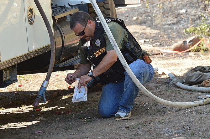 Det. Marc Smith with Hood River County Sheriff's Office collects hollow shell casings as evidence at an unofficial shooting range near the Neal Creek Fire scene Thursday to send to state investigators. The fire, which has been declared human cased, was contained over the weekend.
