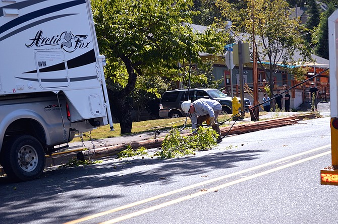 A Pacific Power staffer works on scene at a fallen electric line on 13th St. at Tsuruta Park Friday afternoon.