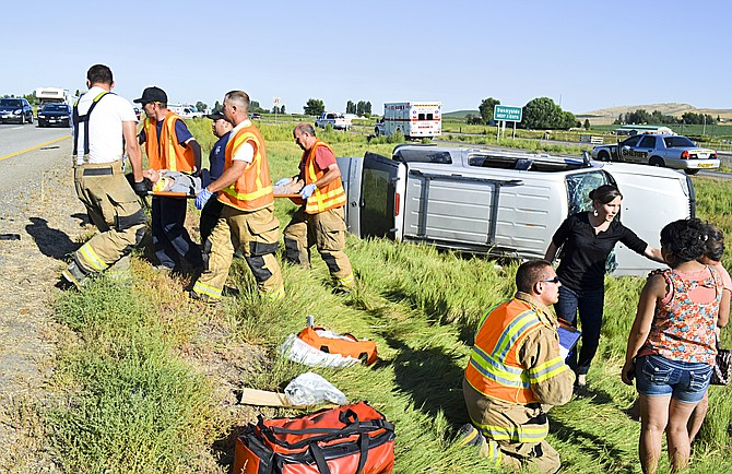 Yakima County Fire District No. 5 responders and passing motorists assist Friday afternoon at a crash scene on Interstate 82 near Sunnyside. The passenger in the 2004 Mercury Mountaineer, 12-year-old Jessica Bernal of Wapato, was injured and taken to Sunnyside Community Hospital. The driver, Maria T. Torres, 34, also of Wapato, was uninjured. The Mountaineer was eastbound at milepost 62 when the left rear tire deflated, the Washington State Patrol said. Torres was cited for driving with the wheels off the roadway.
