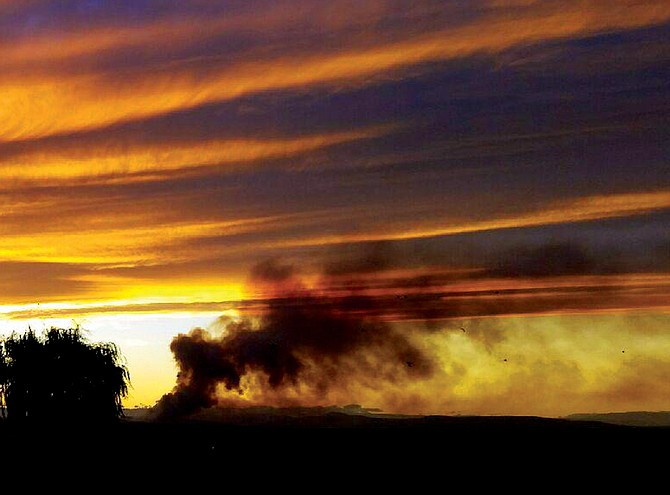 Smoke generated by a large fire burning along U.S. Highway 97 billows into the evening sky near Toppenish late Sunday evening.