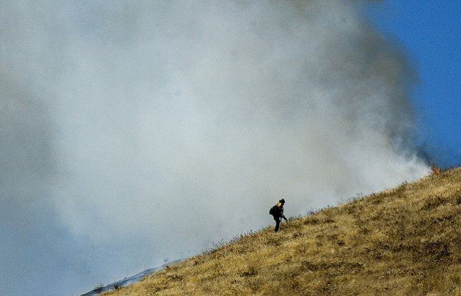 An Oregon Department of Forestry firefighter works up the side of a grass fire along Seven Mile Hill Road Tuesday afternoon. An audit has found the wildfire workload has outpaced staffing.
