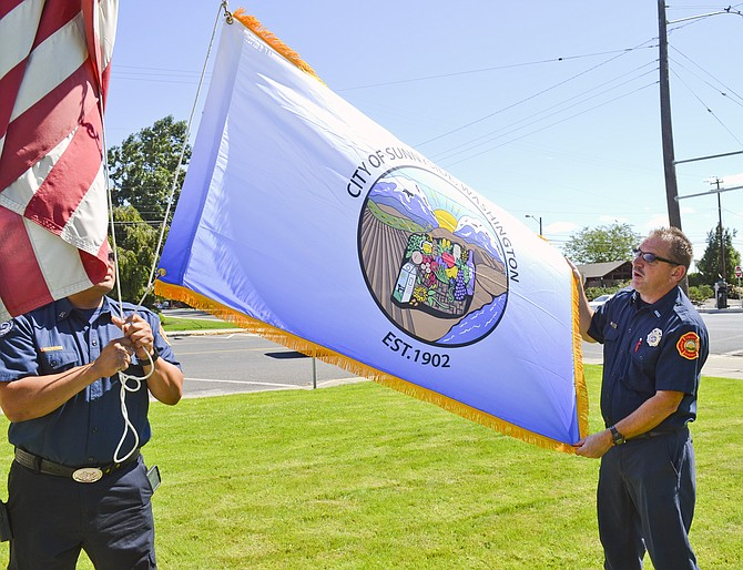 Tony Castillo and Dennis Blumer of the Sunnyside Fire Department raise the city's official flag over City Hall for the first time yesterday.