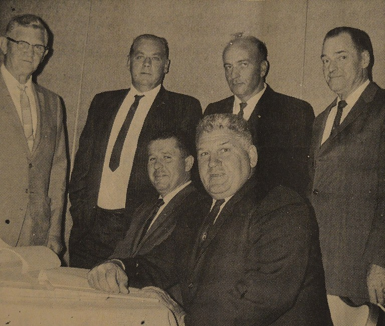 September 1, 1966 — This gathering marks the start of a major bridge project for Cascade Locks. Holding the papers for a complete renovation of the decking and approaches for the Bridge of the Gods is Harry Cramblett, seated in the foreground, who is president of the Port of Cascade Locks Commission. Others standing, from left, are N.W. Haner, engineer for the port, Paul Scott and Willis A. Hill, the winning bidders, and G.W. Nolan, secretary-treasurer of the port. Seated next to Cramblett is Richard Roberts, Port manager. Including engineer fees, the project will cost some $380,000. It involves replacing old wooden decking, widening the traveled surface and improving approaches.