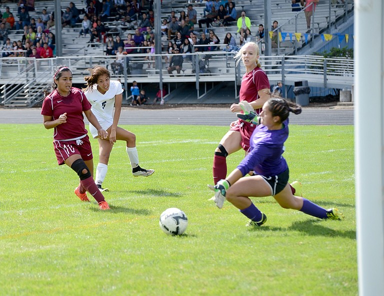 MCLOUGHLIN HIGH SCHOOL didn't stand much of a chance against the HRV girls soccer team during the Eagles' home-opener at Henderson Community Stadium on Saturday, where HRV dominated possession and implemented a relentless attack that scored six goals in the final 23 minutes of the first half. HRV would go on to win the nonconference game 8-0. Although it was against a 4A team that won't do much to improve the team's ranking, nonconference wins will be important for the Eagles this season as they aim to improve their seeding as they anticipate another appearance in the postseason this year. Above left: senior forward Cielo Rivera (white jersey), sneaks one by McLoughlin goalkeeper Mallory Copeland.