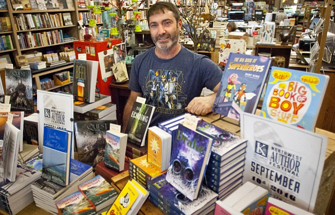 Joaquin Perez, stands behind a display of books by authors attending the Northwest Author Festival at Klindt's Booksellers and Stationers on Saturday, Sept. 10.