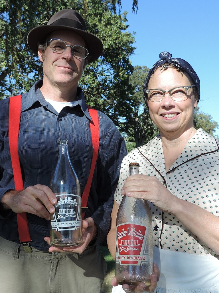 """""""Cemetery Tales"""" performers Matt Rankin and Kathy Peldyak, as Bill and Hazel Bailey, mid-20th century owners of Hood River Bottling Company, hold original bottles that fellow cast member Niko Yasui found in his barn last weekend. The Baileys will display the bottles as part of their """"Cemetery Tales"""" segment Sept. 9-11; see Happenings for details."""