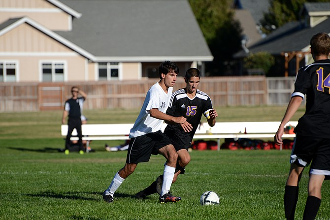 HORIZON'S SOCCER TEAM, pictured in action during Monday's game against Upqua Valley Christian/Melrose Christian, will be defending the 1A title with a roster half the size of what they had during last year's championship run. Quinn Roetcisoender (white jersey) moves the ball past an Umpqua/Melrose defender.