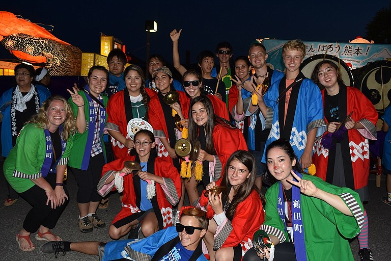 Group members, dressed in their festival jackets, pose with townspeople as they prepare for the parade.