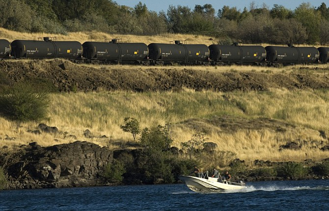A fishing boat set up to work with gillnets motors down the Columbia River in The Dalles as a tanker train, typically used to transport oil by rail, waits on a Burlington Northern Santa Fe side line near Dallesport for the eastbound Amtrak passenger train to pass.