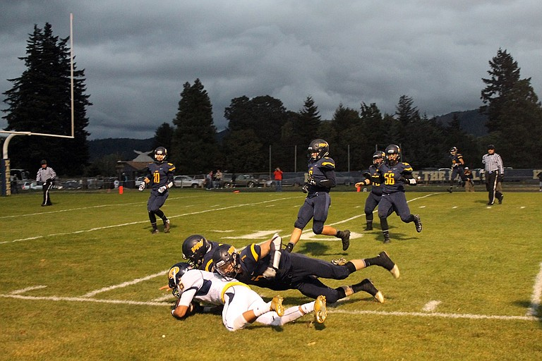 THE HALL OF FAME GAME for the HRV football team was one of the better performances for the Eagles, though the 42-12 result in Bend's favor does not indicate it at first glance. HRV was able to hold the Lava Bears to a 20-6 margin until the final minute of the third quarter, however. Above, Chris McElwee (dark jersey) helps tackle Bend receiver Levi Cockrum.