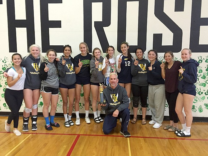 THE HRV VOLLEYBALL TEAM and Head Coach Scott Walker celebrates and poses with their championship trophy after sweeping the competition at a tournament in Parkrose on Saturday.