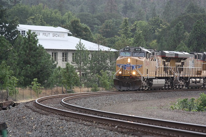 An eastbound Union Pacific freight train rolls through Mosier past the old Mosier Fruit Growers building. UP proposes to build two sets of tracks through this area rather than the existing single mainline as seen here. A total of just over four miles of new track would be put into place if the railroad's extension project goes forward. On Sept. 26, the Wasco County Planning Commission voted 5-2 to approve the project, with numerous conditions.