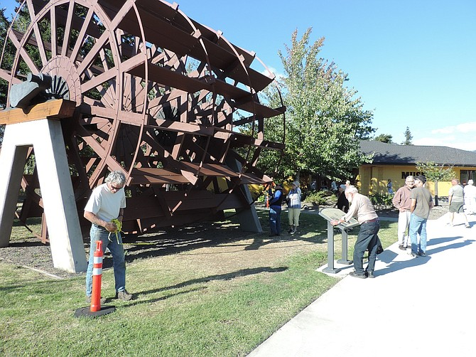 Project Manager Ken Elliot of Scheupbach Construction removes the yellow tape at the ribbon cutting ceremony of the restored M.F. Henderson wheel at the History Museum of Hood River County Sept. 22.