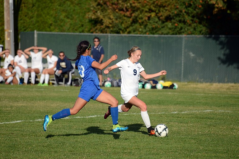 AUDREY MARBLE, who scored a hat trick in a span of just five minutes during Tuesday's game against Pendleton, dribbles the ball in Thursday's home contest against Woodburn (above photo, wearing No. 9), during which she would also score a goal.