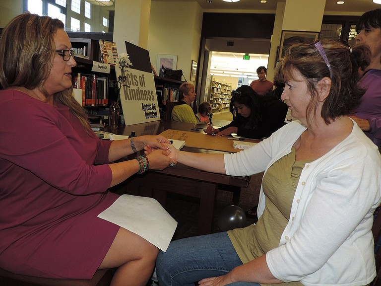 AROMATHERAPIST Amy Nielsen of Carson provides a hand massage to Jayne Mederios during the Happiness Month kickoff at Hood River Library as an act of kindness.