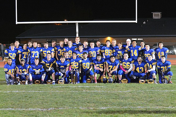 Tonasket football team poses with Battle for the Bell trophy after edging Oroville, 20-16, on Friday.