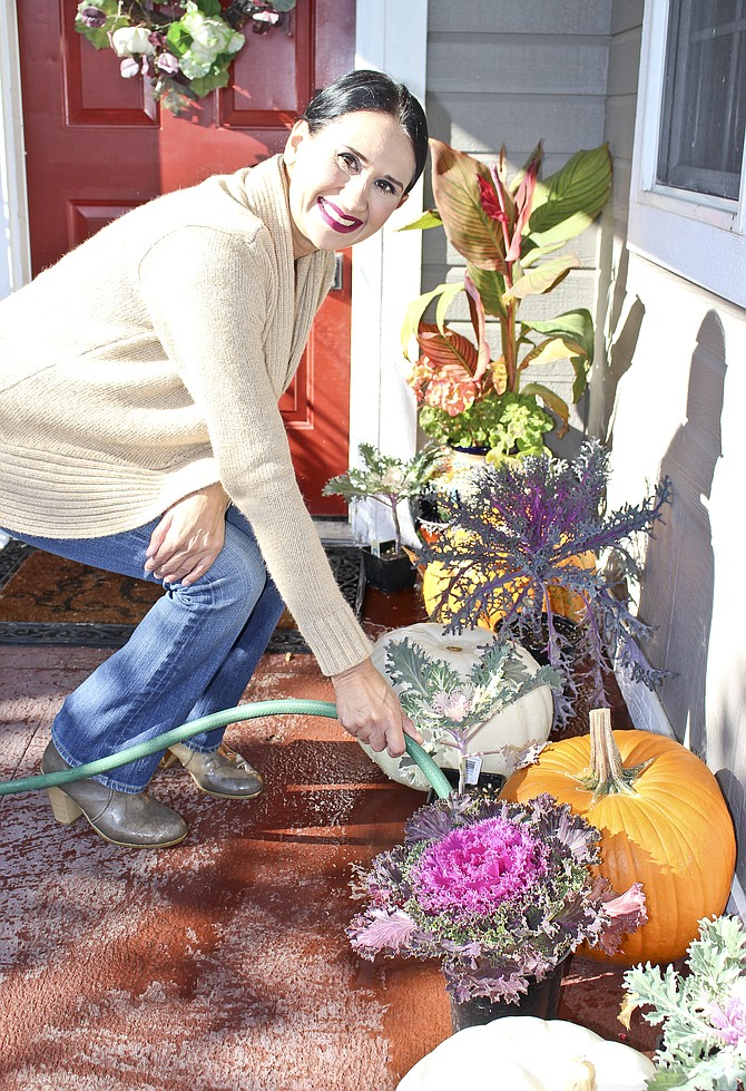 Nora Gonzales of South Ninth Street tends to the fall motif featured on her front porch.