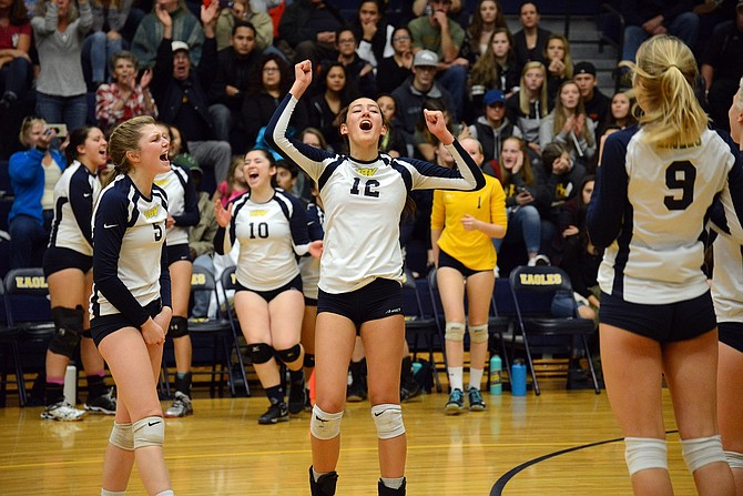 Shae Duffy (center) raisers her arms in jubilation and celebrates with teammate Emily Curtis (No. 5) after HRV wins a point during Saturday's first-round OSAA 5A playoff game against Ashland. The Eagles swept the Grizzlies in three sets to advance to the eight-team tournament for the first time since 1993.