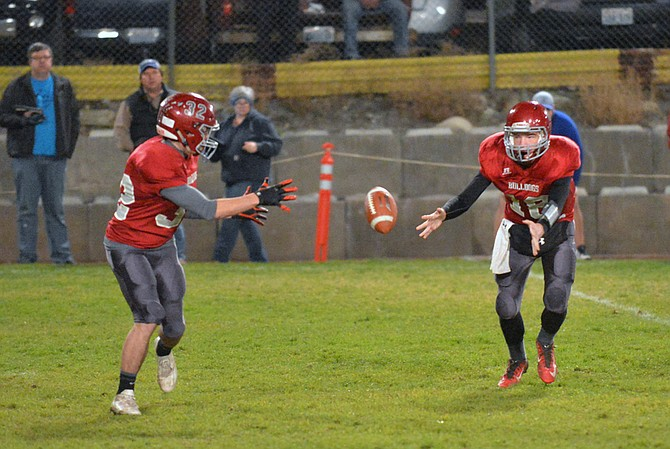 Okanogan High School quarterback Alex Nelson pitches to Greyson Fields during game with La Salle on Friday. The Lightning won, 35-20.