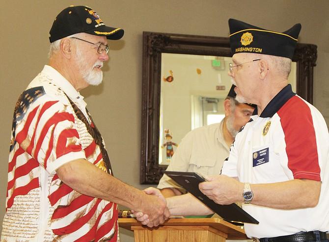 Richard Zook receives a heroism award from Post Commander Robert Gates.