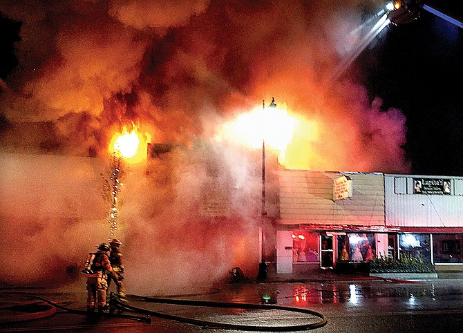 Firefighters battle the downtown blaze that destroyed two storefronts Saturday night.