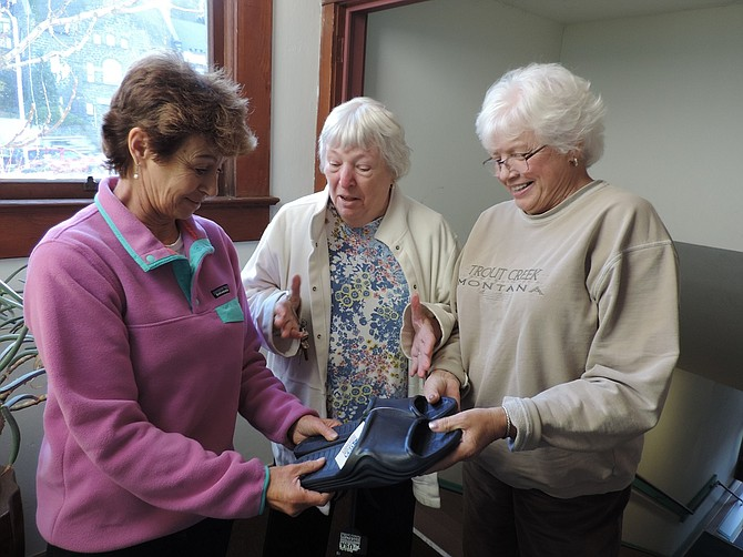 SHELTER SERVICES committee member Bev Carpenter, center, presents footwear to be used by guests, to co-directors Jan Miller, right, and Carole Dearhart.
