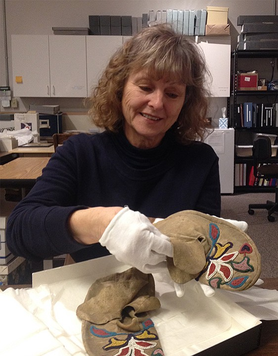 DR. LYNN Orr assesses a pair of moccasins recently donated to the History Museum of Hood River, which she has directed for two years.