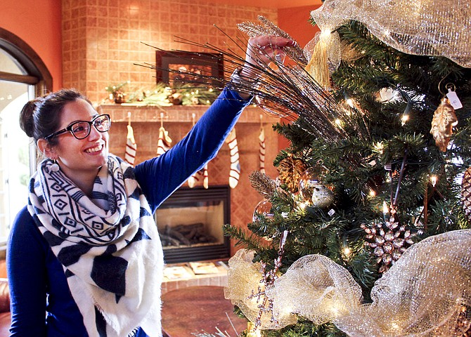 Milbrandt Vineyards Director of retail sales Tara Divers adds one more ornament to the tasting room Christmas tree. The Prosser winery is one of more than 50 in the area hosting open houses through Sunday.