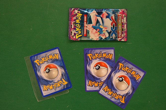 The authentic Pokémon card — seen at left — sports a blue back, whereas the counterfeit cards look more purple. At top is a counterfeit Pokémon pack. Hood River Hobbies has seen an uptick in counterfeits and warns parents to be on the lookout.