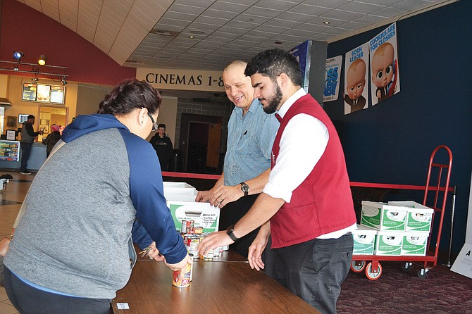 Daniel Van Corbach, right, and Yean Casillas received canned food donations Saturday morning during a free film showing event at Grand Cinemas Yakima Valley in Sunnyside. The items will benefit local food banks to serve those in need this holiday season.